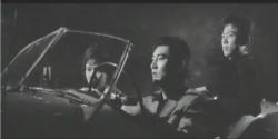 二人を車に乗せて運転している金田一