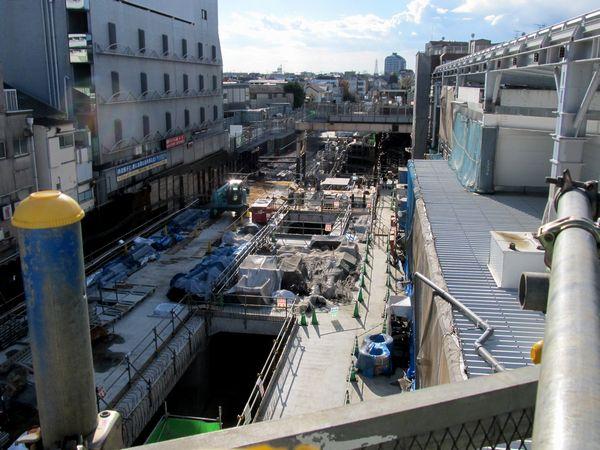 小田原寄りではトンネル最上層部の構築が大詰め。右側の白い鉄骨は本設駅舎の一部。