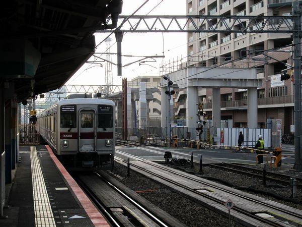 竹ノ塚駅に到着する東部10000系電車と建設中の下り急行線高架橋