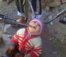 幼児に銃を向ける