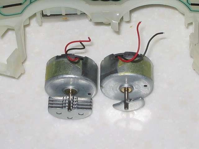 DS3 Dualshock3 デュアルショック3 Wireless Controller Black CECHZC2J A1 分解作業、振動モーターの配線切断後、基板固定用白いプラスチック台座から取り外した振動モーター、画像左側がコントローラー持ち手左側配置の振動モーター(半円柱形状の金属製の重りの枚数が多い側)、画像右側がコントローラー持ち手右側配置の振動モーター(半円柱形状の金属製の重りの枚数が少ない側)