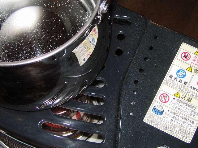 石油ストーブの上に置いた、水と食酢を入れたエルマース ステンレス製 広口 ケットル 3.2L H-2042、注ぎ口先を灯油タンクと反対側の方向に向けている