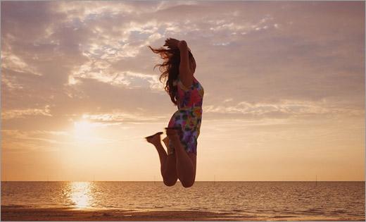 夕暮れの海でジャンプする女の子